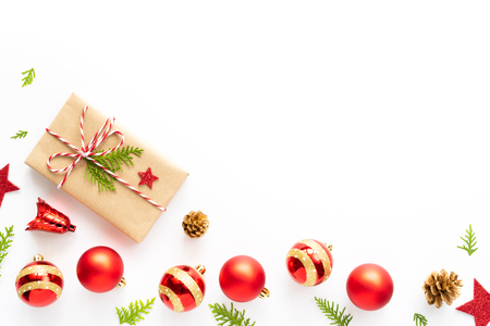 Christmas and New Years composition. Top view of Gift box, pine cones, red star and bell on a wooden white background.