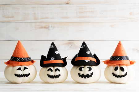 White ghost pumpkins with witch hat on white wooden borad background with bat. halloween concept.
