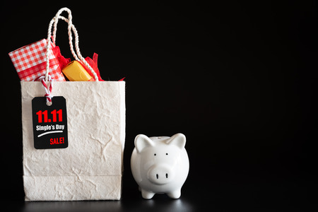 Online shopping of China, 11.11 single day sale concept. Red ticket 11.11 single day sale tag hanging on shopping bag with gift boxes and piggy bank.