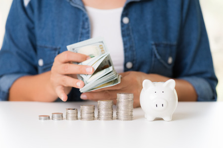 Woman hand counting America dollars banknotes money  with stack of coins and piggy bank. Saving money wealth and financial concept.