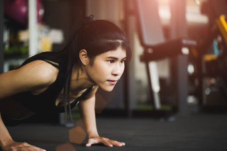 Asian young woman doing push-ups at the gym. Muscular female doing pushups. exercise and healthy lifestyle concept.