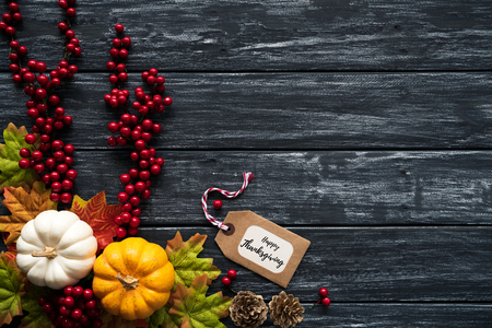 Top view of  Autumn maple leaves with Pumpkin and red berries on old wooden backgound. Thanksgiving day concept. Stock Photo