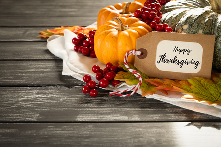 Autumn maple leaves with Pumpkin and red berries on old wooden backgound. Thanksgiving day concept. Stock Photo