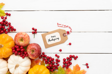 Top view of  Autumn maple leaves with Pumpkin and red berries on white wooden backgound. Thanksgiving day concept.