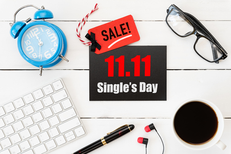 Online shopping of China, 11.11 single day sale concept. Red and black ticket with coffee cup, keyboard computer and mouse on white wooden background. Shopping concept.