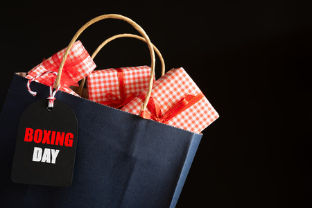 Boxing day Sale text on a black tag with shopping bag and gift box on black background. Online Shopping concept.