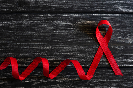 Closeup red ribbon awareness on black wooden table background  for World Aids day campaign.