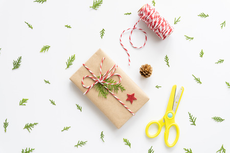 Christmas background concept. Top view of Christmas gift box with tag message, red star and pine cones on white background.