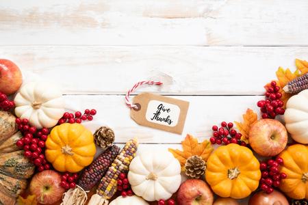 Bovenaanzicht van herfst esdoorn bladeren met pompoen en rode bessen op witte houten achtergrond. Thanksgiving-dagconcept.