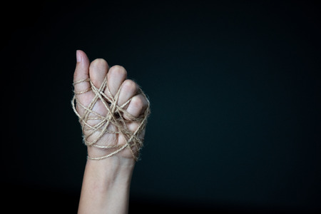a woman hand tied with wire on dark background in low key. international human rights day concept.