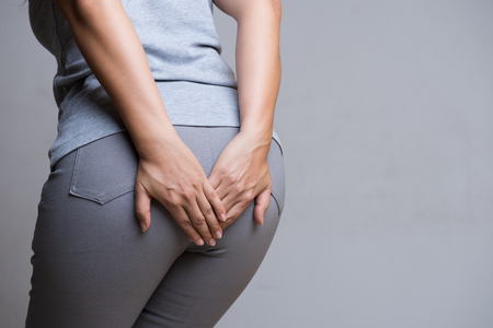 Woman suffering from hemorrhoids and hand holding her bottom because having Abdominal pain. Health care concept.
