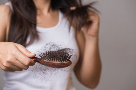Healthy concept. Woman show her brush with long loss hair and looking at her hair.