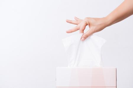 Gezondheidszorgconcept. Vrouw die wit papieren zakdoekje met de hand plukt uit tissuedoos. Stockfoto