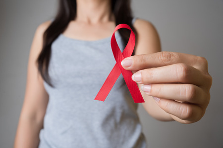 Closeup woman hand holding red ribbon HIV, world AIDS day awareness ribbon. Healthcare and medicine concept. Stock Photo