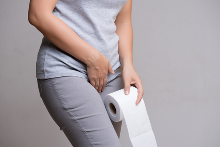 Woman hand holding her crotch lower abdomen and tissue or toilet paper roll. Disorder, Diarrhea, incontinence. Healthcare concept. Stock Photo