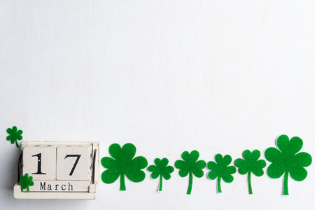 Block calendar for St Patrick's Day, March 17, with green clover leaf, green water and paper tag on white wooden background Stock Photo