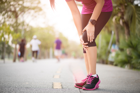 Runner sport knee injury. Woman in knee pain while running work out in park. Health care concept.