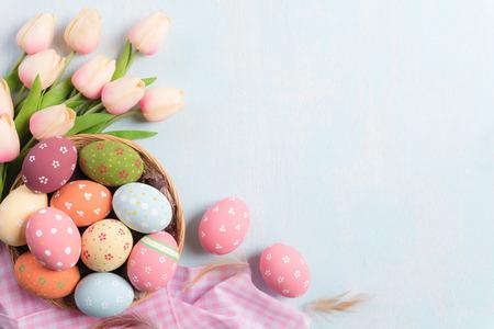 Frohe Ostern! Bunte Ostereier im Nest mit rosa Tulpen und Feder auf Holzhintergrund des blauen Himmels.