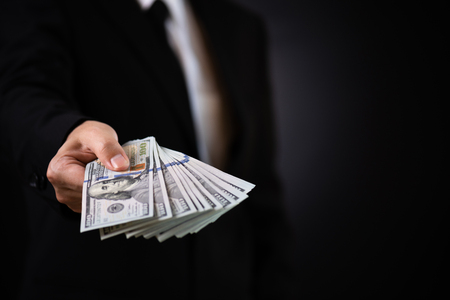 Businessman with money in hand and giving money as a bribe, US dollar (USD) bills - investment, success and profitable business concepts. Stok Fotoğraf