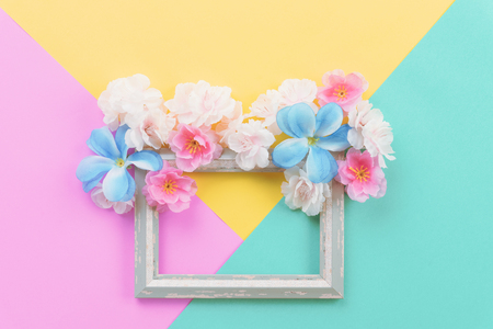 Summer composition. Empty frame and flowers flat lay on yellow, green and pink pastel background with copy space. Stock Photo