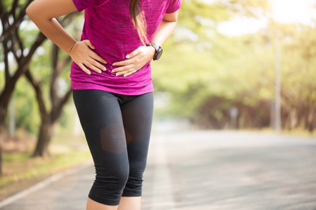 Sport girl have stomach pain after jogging work out in park. Health care concept.