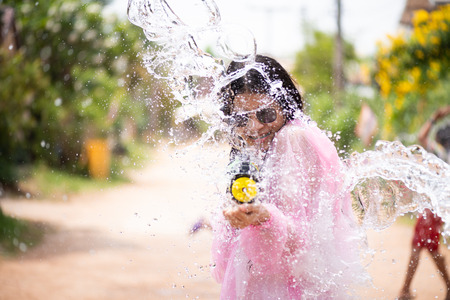 Young happy beauty Asian girl with water gun wearing summer shirt in Songkran festival - water festival in Thailand. Stock Photo