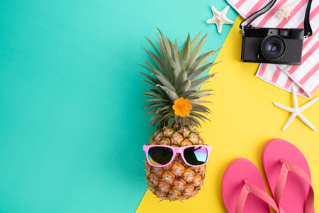 Beach accessories retro film camera, pineapple, sunglasses, flip flop starfish beach hat and sea shell on green and yellow background for summer holiday and vacation concept.