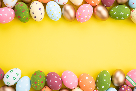 Buona Pasqua! Chiudere le uova di Pasqua colorate su sfondo di carta gialla. Famiglia felice che si prepara per la Pasqua.
