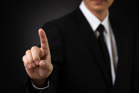 Businessman pointing with his finger against black background. Business, technology and internet concept.