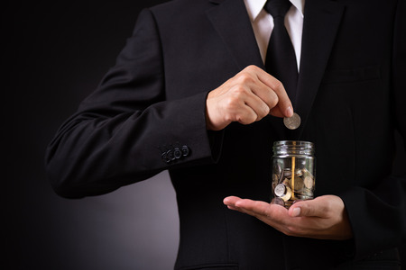Businessman in suit is hand putting coin into jar. Finance Savings, investment, success and profitable business concept
