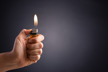 Close up woman hand holding a burning lighter in the dark background.