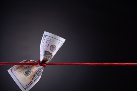 Amerikanischer Dollar gefesselt im roten Seilknoten auf dunklem Hintergrund mit Kopienraum. Geschäftsfinanzen, Spar- und Insolvenzkonzept. Standard-Bild