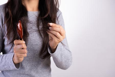 Gesundes Konzept. Frau zeigt ihre Bürste mit geschädigtem langem Haarausfall und betrachtet ihr Haar.
