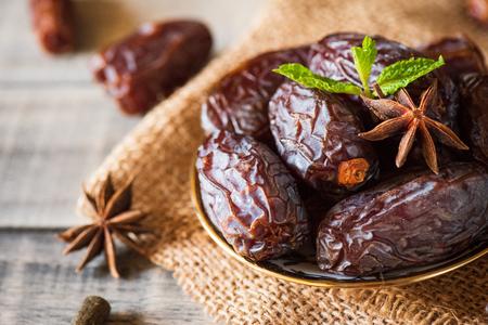 Concept de nourriture et de boissons du Ramadan. Dates fruits et feuilles de menthe verte dans un bol sur fond de table en bois. Banque d'images