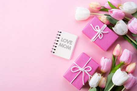 Happy mothers day concept. Top view of pink tulip flowers, gift box and note book with LOVE MOM text on pink pastel background. Flat lay.