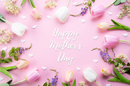 Happy mothers day concept. Top view of pink tulip flowers in frame with happy mother's day text on pink pastel background. Flat lay. Imagens