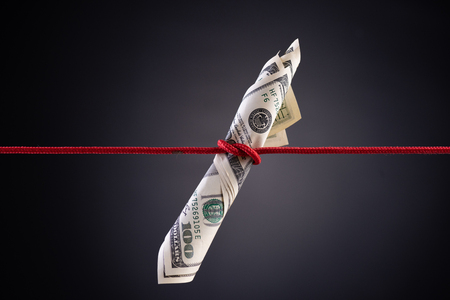 American dollar tied up in red rope knot on dark background with copy space. business finances, savings and bankruptcy concept. Archivio Fotografico