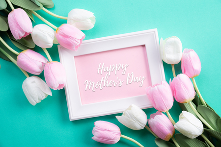 Happy mothers day concept. Top view of pink tulip flowers and white picture frame with happy mother's day text on green pastel background. Flat lay.
