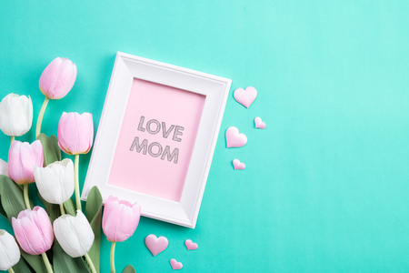 Happy mothers day concept. Top view of pink tulip flowers and white picture frame with LOVE MOM text on green pastel background. Flat lay. Banco de Imagens