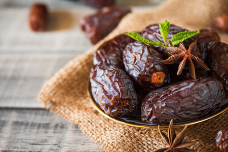 Ramadan food and drinks concept. Dates fruit and green Mint leaves in a bowl on wooden table background. Stock Photo