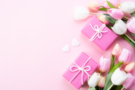 Happy mothers day concept. Top view of pink tulip flowers, gift box on pink pastel background. Flat lay. Stock Photo