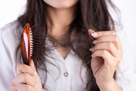 Concetto sano. La donna mostra la sua spazzola con i capelli danneggiati a perdita lunga e guardando i suoi capelli.