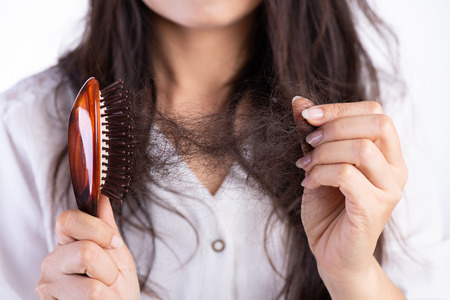Healthy concept. Woman show her brush with damaged long loss hair and looking at her hair. Banco de Imagens - 122147075