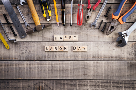 Labour Day, Wooden Block calendar with many handy tools on wooden background texture.
