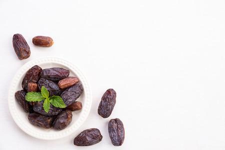 Ramadan-Konzept für Speisen und Getränke. Dattelfrucht und grüne Minzeblätter in einer Schüssel auf einem weißen Holztischhintergrund. Ansicht von oben, flach.