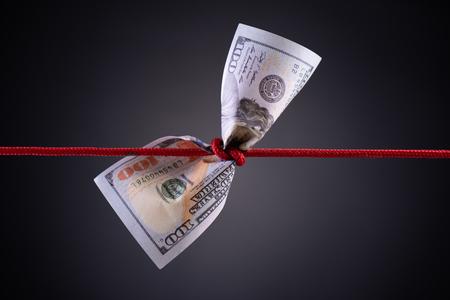 Amerikanischer Dollar gefesselt im roten Seilknoten auf dunklem Hintergrund mit Kopienraum. Geschäftsfinanzen, Spar- und Insolvenzkonzept.