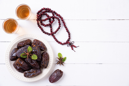 Ramadan food and drinks concept. Wood rosary, tea and dates fruit on a white wooden table background. Top view, Flat lay.
