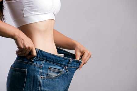Young slim woman in oversized blue jeans. Fit woman wearing too large pants. Healthcare and woman diet lifestyle concept to reduce belly and shape up healthy stomach muscle.