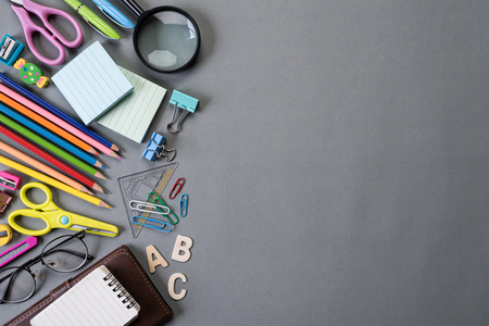 Education or back to school Concept. Top view of Colorful school supplies with books, color pencils, calculator, pen cutter clips and green apple on gray background. Flat lay. Stock Photo
