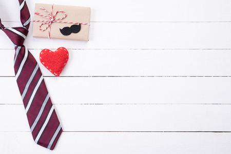 Concetto di festa del papà felice. Vista dall'alto della cravatta blu, bella confezione regalo, cuore rosso con baffi uomo su sfondo bianco tavolo in legno. Disposizione piatta.